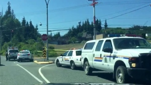 Police tape and officers surround the scene of a fatal officer-involved shooting at Granville Street and Highway 19 in Port Hardy. July 8, 2015. (Twitter)