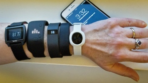 Fitness trackers, from left, Basis Peak, Adidas Fit Smart, Fitbit Charge, Sony SmartBand, and Jawbone Move, are posed for a photo next to an iPhone, in New York on Dec. 15, 2014. (AP / Bebeto Matthews)