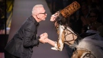 French designer Jean Paul Gaultier and a model wearing one of his creation about to kiss during the presentation of his fall-winter 2015/2016 Haute Couture fashion collection, in Paris, Wednesday, July 8, 2015. (AP /Kamil Zihnioglu)