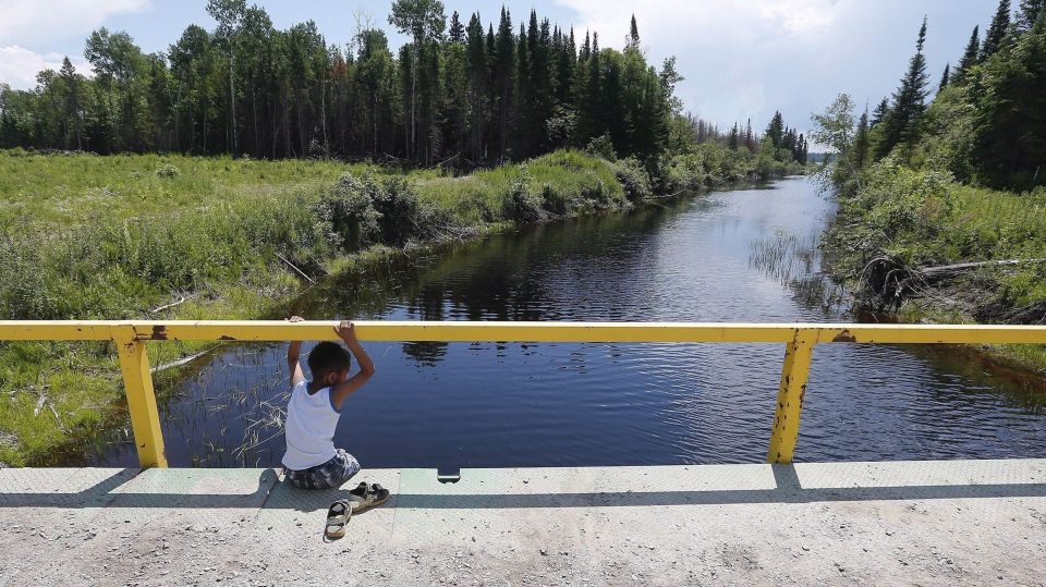 A boy from the Shoal Lake 40 First Nation sits on a bridge over a channel on on Thursday, June 25, 2015. (John Woods / THE CANADIAN PRESS)