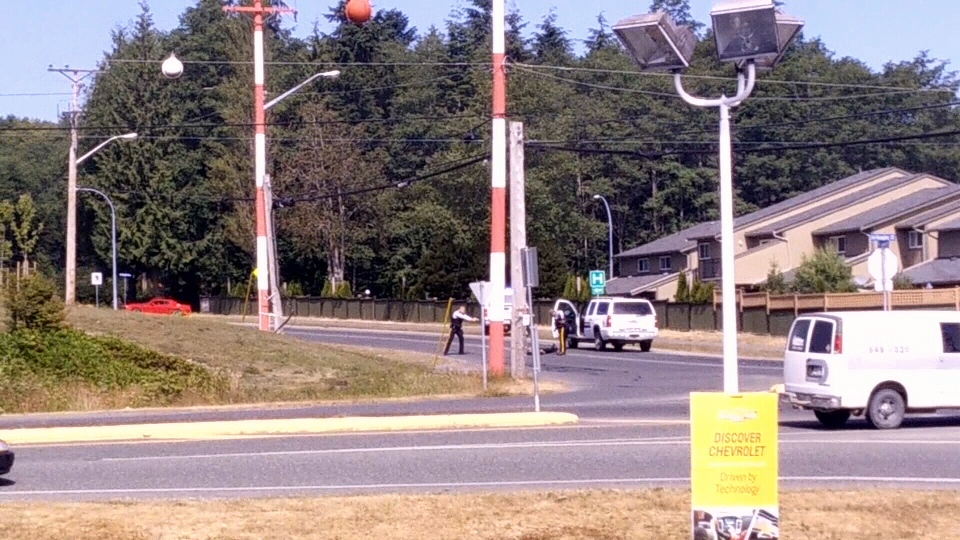 Police draw a gun on a suspect at the intersection of Highway 19 and Granville Street in Port Hardy, B.C. Thursday, July 9, 2015. (RCMP Handout)