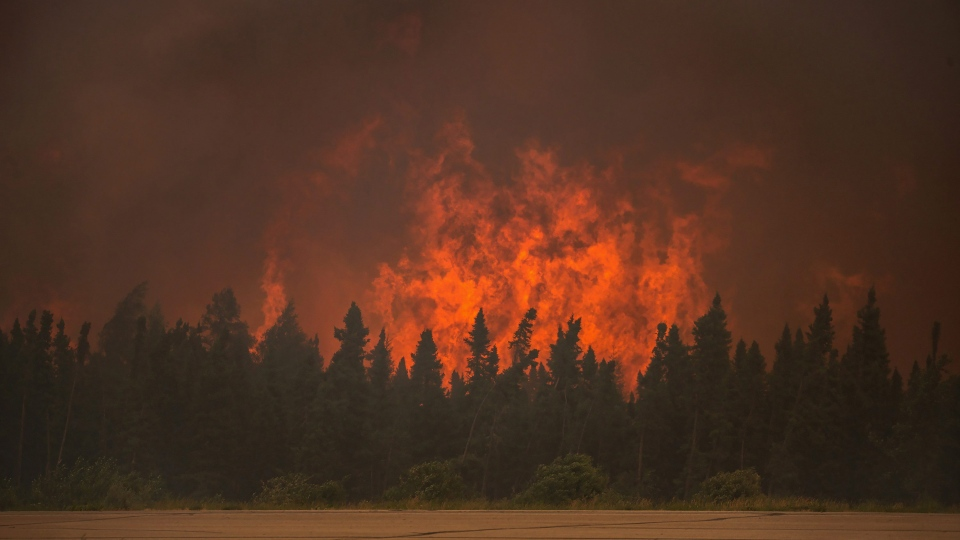 A wildfire blazes beyond a tree line in the La Ronge, Sask., area in this July 5, 2015 handout photo. (THE CANADIAN PRESS/HO/Sask. Ministry of Environment, Corey Hardcastle)