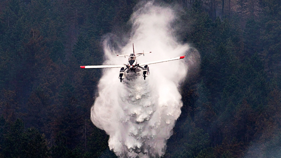 A water bomber drops water on a hillside in West Kelowna, B.C. Friday, July, 18, 2014. A pilot battling wildfires in British Columbia's Interior escaped serious injury after crashing his single-engine plane into a lake while scooping water, says a spokesman for the Transportation Safety Board. (Jonathan Hayward / THE CANADIAN PRESS)
