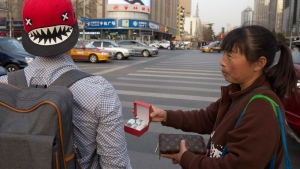 In this photo taken Friday, March 20, 2015, a street vendor hawks counterfeit branded items to tourists on the streets of Beijing. Counterfeiting is a big business, by one estimate, the global market for fakes will hit $1.7 trillion this year. (AP/Ng Han Guan)