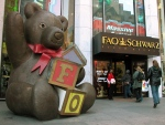 In this Nov. 10, 2003 file photo, customers pass a statue of a teddy bear and a doorman dressed as a toy soldier as they enter the FAO Schwarz on Fifth Avenue in New York. (AP Photo/Rich Kareckas, File)