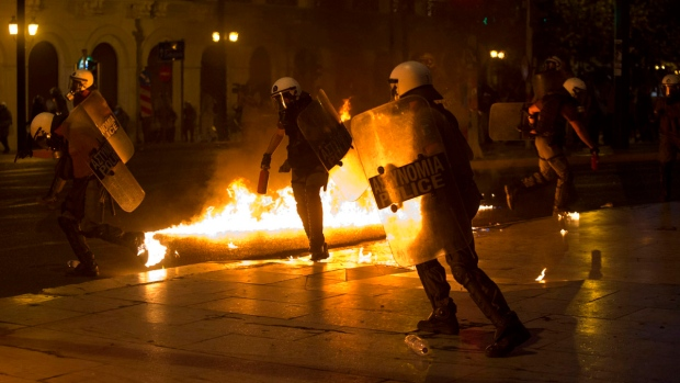 Riot policeman try to avoid a petrol bomb thrown by anti-austerity protesters in Athens, Wednesday, July 15, 2015. (AP / Petros Giannakouris)