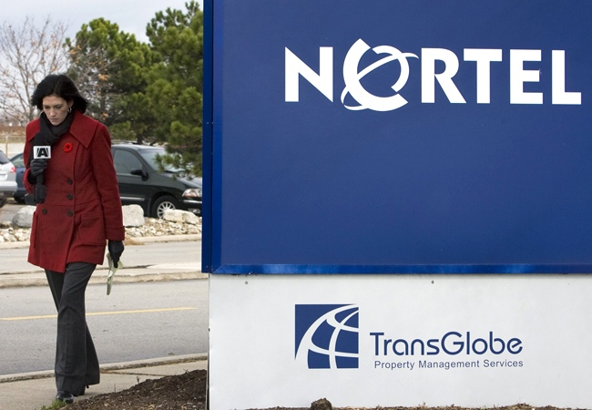 A reporter for 'A' News walks past the Nortel office tower sign in Etobicoke, west-end Toronto, on Monday, Nov. 10, 2008. (Nathan Denette / THE CANADIAN PRESS)
