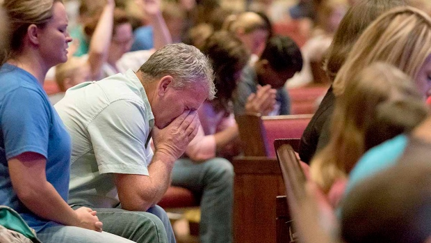 Corey Groce puts his face in his hands as he prays during a prayer vigil at Redemption Point Church for the victims of shootings at a recruiting center and another U.S. military site a few miles apart in Chattanooga, Tenn., Thursday, July 16, 2015 (Doug Strickland / Chattanooga Times Free Press)
