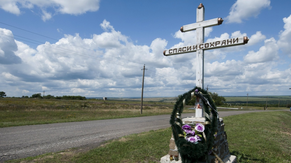 An Orthodox cross with a sign reading Save and Guard is placed at the site of the crashed Malaysia Airlines Flight 17 plane, near the village of Hrabove, eastern Ukraine on July 16, 2015. (AP / Antoine E.R. Delaunay)