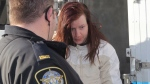 Victoria Henneberry, 28, is escorted into a Halifax court, on Feb. 28, 2014. (THE CANADIAN PRESS/Mike Dembeck)