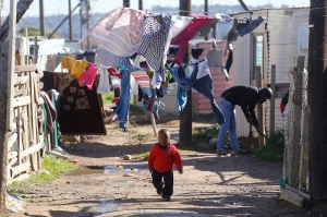A child walk on a dirt road near his home as people nearby paint shacks with white fire retardant paint as part of their contribution to International Nelson Mandela day celebrating former South African president Mandela birth day in the township of Nomzamo , South Africa, Saturday, July 18, 2015. (AP/Schalk van Zuydam)