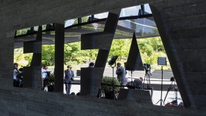 Journalists are reflected in the FIFA logo as they wait in front of the FIFA headquarters in Zurich prior to the press conference of the extraordinary FIFA Executive Committee in Zurich, Switzerland, Monday, July 20, 2015. (Ennio Leanza / Keystone)