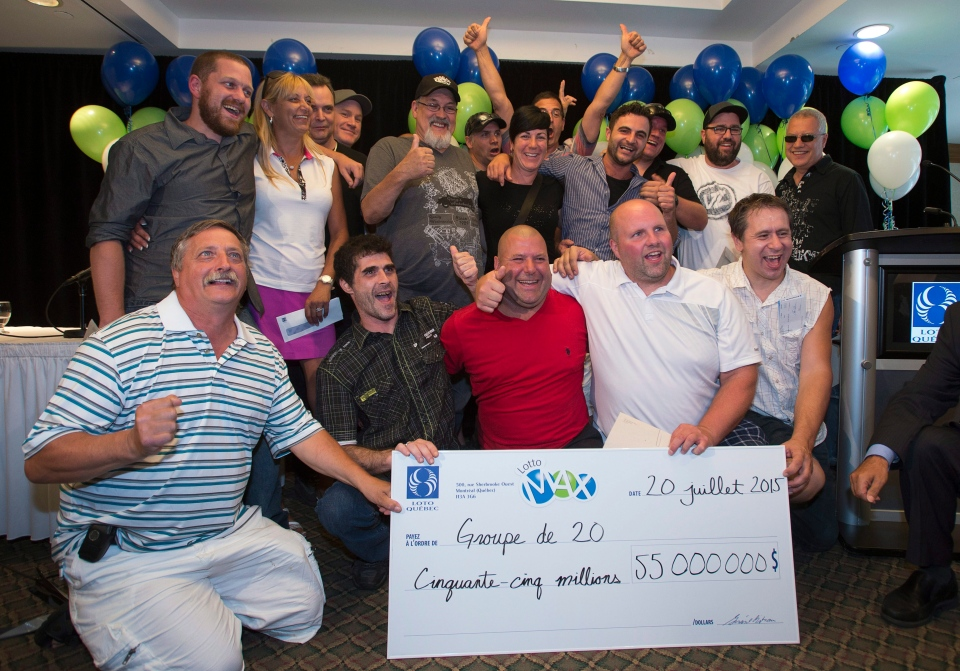 A group of 20 Rona hardware employees pose with their 55 million dollar Lotto Max jackpot cheque, the second largest in Canadian history, at a news conference, in Montreal, Monday, July 20, 2015. (Ryan Remiorz / THE CANADIAN PRESS)