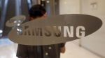 A visitor walks by the logo of Samsung Electronics Co. near its shop in Seoul, South Korea, Tuesday, July 7, 2015. (AP / Lee Jin-man)