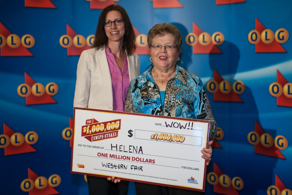 In this photo provided by the OLG, Helena Vermeeren, right, and Deanne Rodrigue, OLG executive director of marketing, pose with Vermeeren's million-dollar cheque in London, Ont. on Tuesday July 21, 2015.