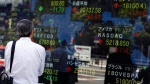 A man looks at an electronic stock board displaying global stock indexes, including Japan's Nikkei 225 index, top center, in Tokyo, Tuesday, July 21, 2015. Most Asian stock markets were modestly higher Tuesday after positive U.S. earnings reports boosted sentiment. (AP Photo/Ken Aragaki)