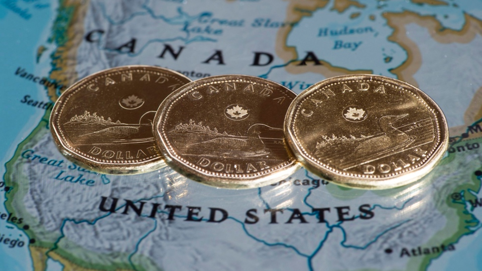 Canadian dollar coins are displayed on a map of North America, January 9, 2014 in Montreal. (Paul Chiasson / THE CANADIAN PRESS)