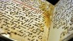 Marie Sviergula, conservator of the University of Birmingham holds a Qu'ran manuscript in Birmingham England on July 22, 2015. (AFP PHOTO / PAUL ELLIS)