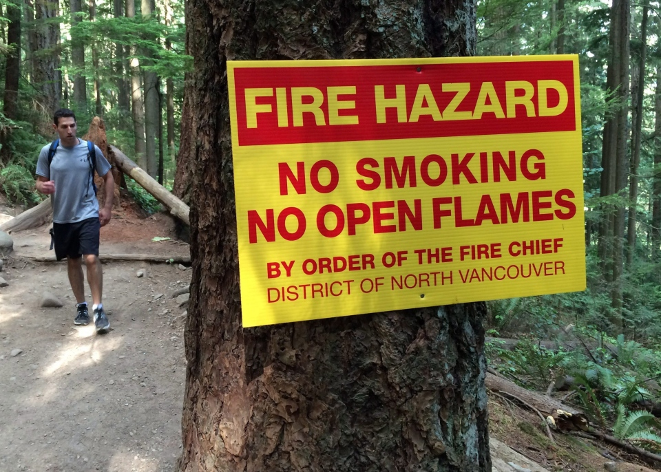 A hiker makes his way past a fire hazard sign on the Baden Powell trail in north Vancouver, Tuesday, July 21, 2015. (Jonathan Hayward / THE CANADIAN PRESS)