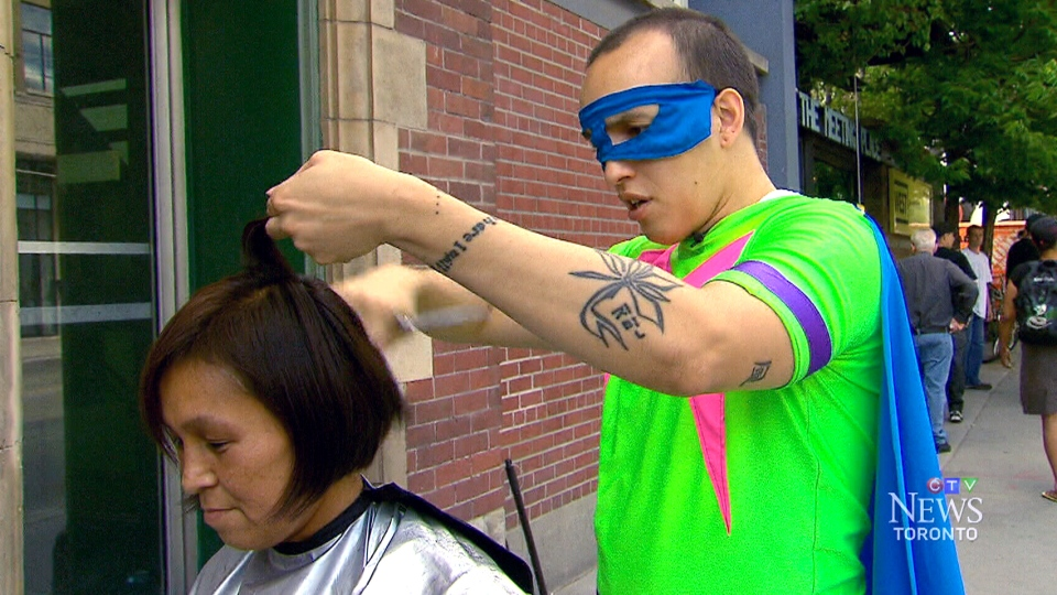 Matthew Genser cuts a person's hair as his superhero alter ego, 'Mazing,' on the streets on Toronto on July 22, 2015.
