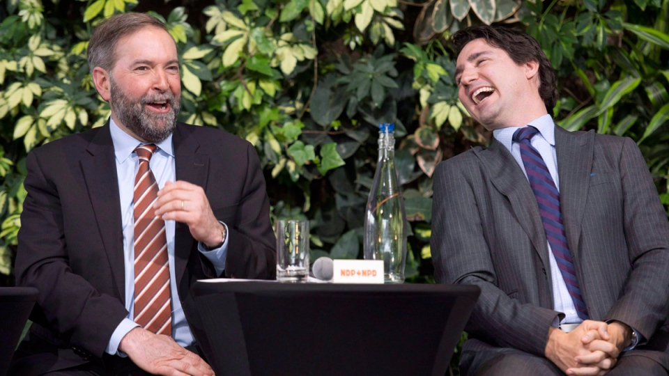 Liberal Leader Justin Trudeau laughs with NDP Leader Tom Mulcair in Ottawa, on March 26, 2014. (THE CANADIAN PRESS / Adrian Wyld)