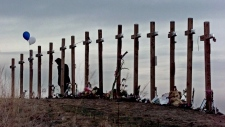 This April 28, 1999 file photo shows a woman standing among 15 crosses posted on a hill above Columbine High School in Littleton, Colo., in remembrance of the 15 people who died during a school shooting on April 20, 1999. (Eric Gay/AP Photo)