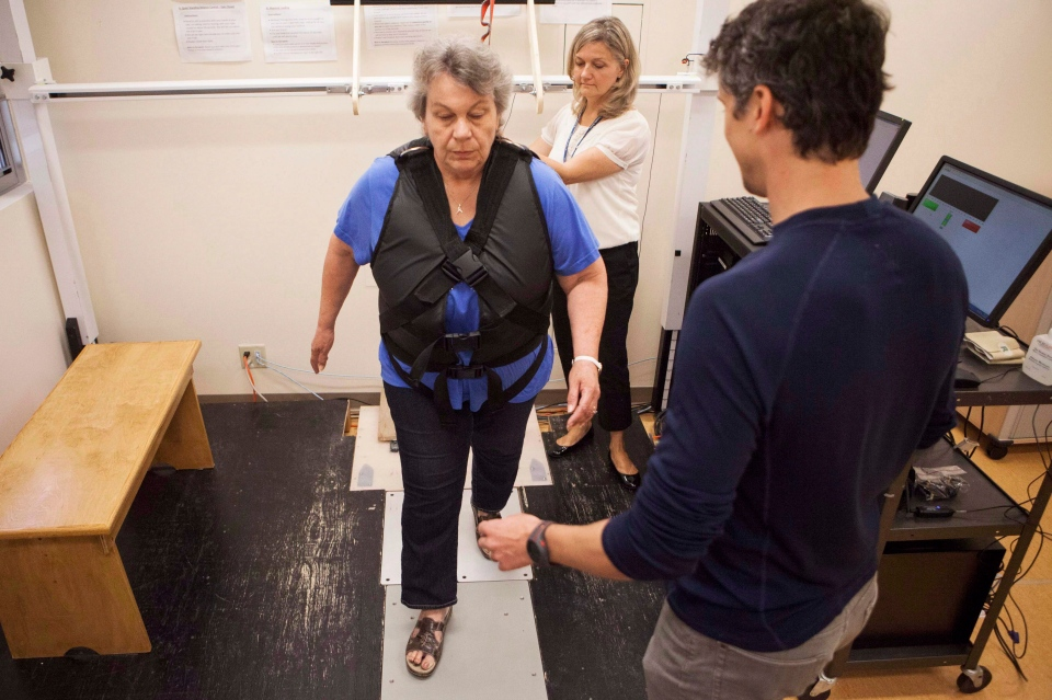Stroke survivor Janet Raymond (centre) is helped by physiotherapist Lou Biasin (front) and Clinical Leader of the Balance and Mobility Clinic Liz Inness in performing exercises in a lean and release balance assessment tool at Toronto Rehab on May 23, 2013. (Jesse Johnston / The Canadian Press)