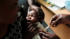 In this Oct. 30, 2009 file photo, a mother holds her baby as she receives a new malaria vaccine as part of a trial at the Walter Reed Project Research Center in Kombewa in Western Kenya. (AP / Karel Prinsloo, File)