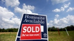 In this June 4, 2015, photo, a sign indicates a site has been sold in a new home development in Nashville, Tenn. The Commerce Department reports on sales of new homes in June on Friday, July 24, 2015. (Mark Humphrey/AP Photo)