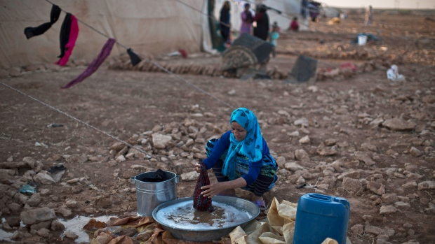 A Syrian refugee woman washes her laundry outside her tent at an informal tented settlement near the Syrian border on the outskirts of Mafraq, Jordan, Thursday, July 23, 2015. (AP / Muhammed Muheisen)