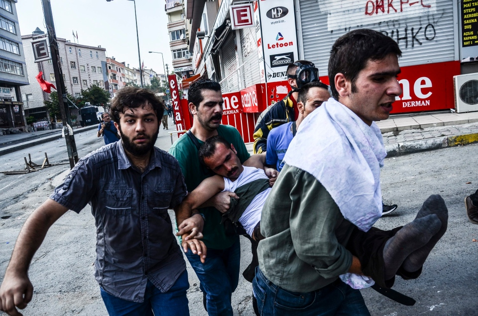 Protesters carry a wounded man in Istanbul, Saturday, July 25, 2015, during clashes between police and protesters denouncing the deaths of 32 people at an suicide bombing Monday in Suruc, southeastern Turkey. Turkish jets struck camps belonging to Kurdish militants in northern Iraq, authorities said Saturday, the first strikes since a peace deal was announced in 2013, and again bombed Islamic State group positions in Syria. (AP / Cagdas Erdogan)