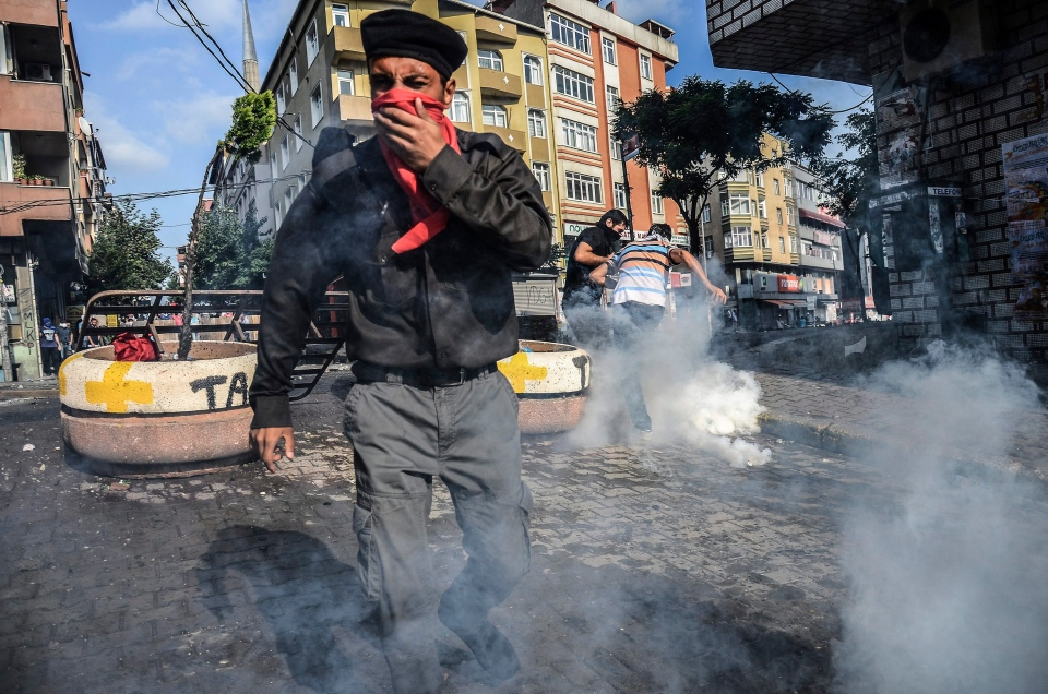 Protesters try to avoid the effects of tear gas fired by police in Istanbul, Saturday, July 25, 2015, during clashes between police and protesters denouncing the deaths of 32 people at an suicide bombing Monday in Suruc, southeastern Turkey. (AP / Cagdas Erdogan)