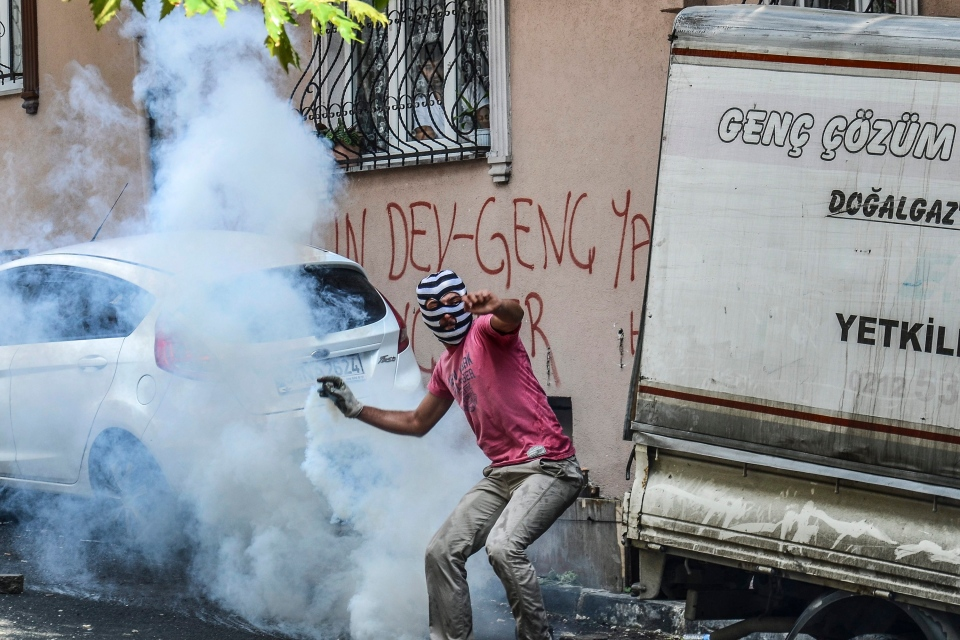 A protester runs to throw back a tear gas canister originally fired by police in Istanbul, Saturday, July 25, 2015, during clashes between police and protesters denouncing the deaths of 32 people at an suicide bombing Monday in Suruc, southeastern Turkey. (AP / Cagdas Erdogan)