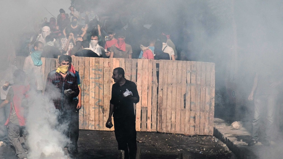Protesters man a barricade, as tear gas fired by police fills the street, in Istanbul, Saturday, July 25, 2015, during clashes between police and protesters denouncing the deaths of 32 people at an suicide bombing Monday in Suruc, southeastern Turkey.  (AP/Cagdas Erdogan)