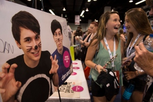 Skylar Sutton, 13, left, reacts after buying items as Charlotte Horne, 13, looks on at the Youtube personality Dan and Phil booth during the 6th annual VidCon at Anaheim Convention Center in Anaheim, Calif. on Thursday, July 23, 2015. (Ed Crisostomo / The Orange County Register via AP)