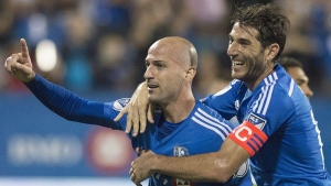 Montreal Impact's Laurent Ciman, left, celebrates with teammate Ignacio Piatti after scoring against the Seattle Sounders during second half MLS soccer action in Montreal, Saturday, July 25, 2015. THE CANADIAN PRESS/Graham Hughes