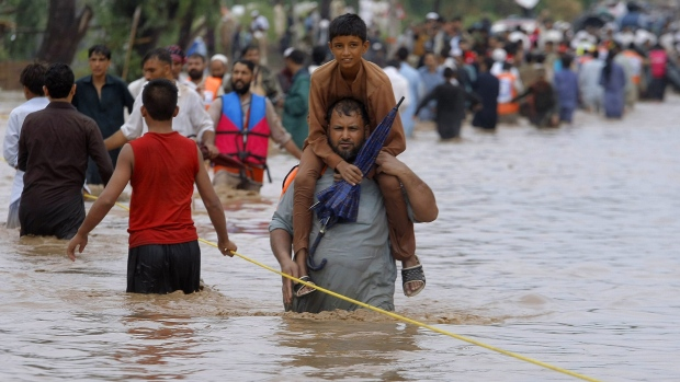 A Pakistani carries his son on his shoulder while he and others cross a flooded road caused by heavy rains in Peshawar, Pakistan, Sunday, July 26, 2015. (AP / Muhammad Sajjad)