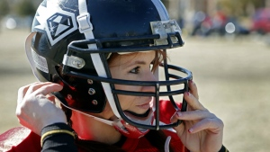 Jen Welter puts her helmet on before the start of the Texas Revolution practice at Bradford Crossing Park in Allen, Texas on Feb. 12, 2014. (The Dallas Morning News / Vernon Bryant)