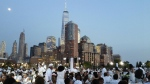 People dressed in white have dinner on Pier 26 along the Hudson River during the Diner en Blanc event in New York on July 28, 2015. Thousands of people attended the world's largest popup picnic, at a location revealed at the last moment. (AP / Verena Dobnik)