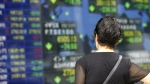 A woman looks at an electronic stock indicator of a securities firm in Tokyo, Tuesday, July 28, 2015. (AP / Shizuo Kambayashi)