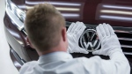 A worker checks the Volkswagen sign on a Passat Variant car during a press tour at the plant of the German manufacturer Volkswagen Sachsen in Zwickau, Germany on Jan. 26, 2015. (AP / Jens Meyer)