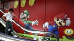 A shopper walks in front of Nintendo's Super Mario characters at an electronics store in Tokyo on July 13, 2015. (AP / Koji Sasahara)