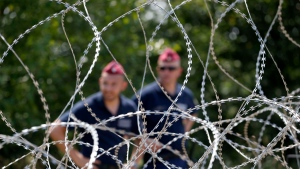 Hungarian police officers guard behind barbed wire near Morahalom, Hungary, Thursday, July 16, 2015. (AP / Darko Vojinovic)