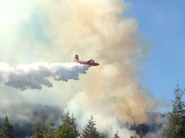 The massive Martin Mars water bomber soared above a wildfire that broke out at Cowichan Lake near Skutz Falls Tuesday, July 28, 2015.