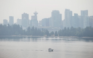 A boat travels out of Burrard Inlet as smoke from wildfires across the province fills the air in Vancouver, B.C., on Monday July 6, 2015. (Darryl Dyck / The Canadian Press)