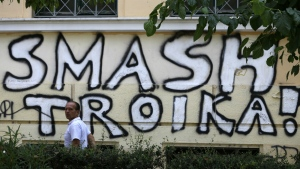 A pedestrian passes graffiti referring to the officials from the European Union, European Central Bank and International Monetary Fund, together known as the troika, in Athens on July 29, 2015. (AP / Thanassis Stavrakis)