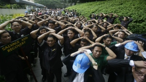 Hotel and office employees cover their heads as they take part in a Metropolitan Manila-wide earthquake drill at the financial district of Makati city east of Manila, Philippines on July 30, 2015. The drill was designed to boost preparedness in the country for an eventual earthquake. (AP / Bullit Marquez)