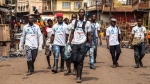 In this file photo taken on Friday, March. 27, 2015, a team of  Sierra Leone health workers walk as they look for people suffering from Ebola virus symptoms or people they can educate about the virus as there country enters a three day country wide lockdown on movement of people do to the Ebola virus in the city of Freetown, Sierra Leone. (AP Photo/ Michael Duff,File)