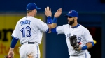 Toronto Blue Jays right fielder Jose Bautista, right, celebrates the win with teammate Justin Smoak (13) after defeating the Kansas City Royals in AL baseball action in Toronto on Thursday, July 30, 2015. Smoak switched his number to 13 from 14 after the Blue Jays acquired starting pitcher David Price. THE CANADIAN PRESS/Nathan Denette