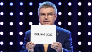President of the International Olympic Committee (IOC) Thomas Bach opens the envelope announcing that Beijing has won the bid to host the 2022 Winter Olympic Games at the 128th International Olympic Committee session in Kuala Lumpur, Malaysia, Friday, July 31, 2015.  (AP / Joshua Paul)